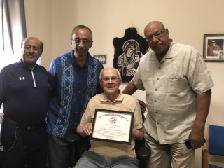 """Father Turenne with his """"TMSAANA Award of Gratitude Certificate"""",  August 2018"""